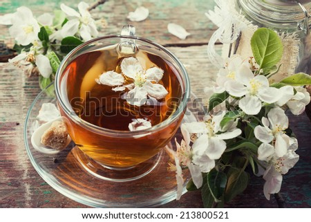 Cup of fresh herbal tea with spring flowers on vintage wooden table. Selective focus, horizontal. Toned image. - stock photo