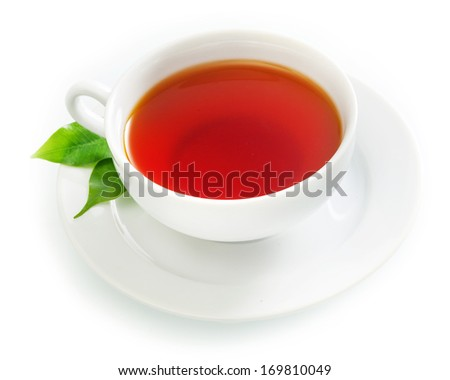 Cup of fresh hot black tea in an elegant plain white cup and saucer with fresh green tea leaves over a white background - stock photo