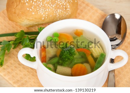 Cup of fresh vegetable soup and bread on a napkin, closeup - stock photo