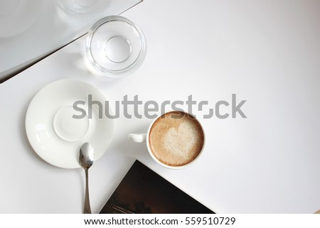 cup of freshly brewed coffee, cappuccino with latte art, glass of water and magazine, slow living, enjoying the little things, delicious flavor and taste, white background