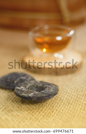 Cup of freshly brewed tea and Beads of Chinese Puer tea
