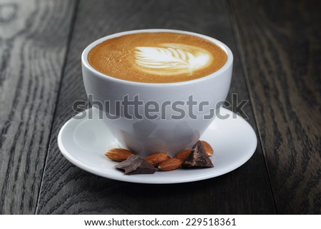 cup of freshly made cappuccino with latte art, on oak table