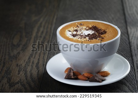 cup of freshly made cappuccino with latte art, on oak table - stock photo