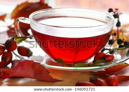 Cup of fruit rosehip tea and autumn leaves and fruits on a table - stock photo
