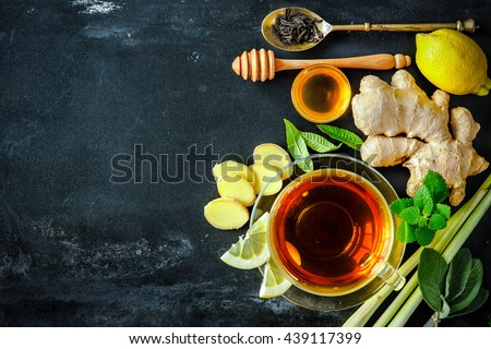 Cup of ginger tea with lemon and honey on slate plate - stock photo