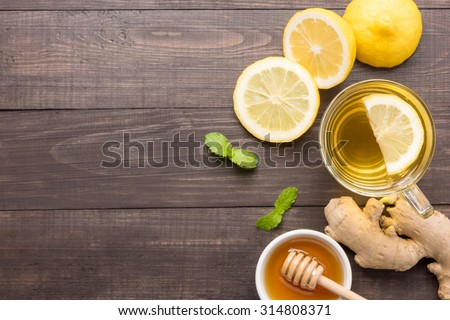 Cup of ginger tea with lemon and honey on wooden background. - stock photo