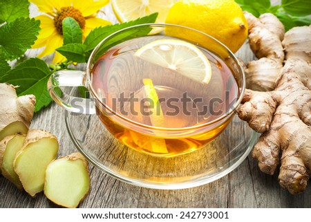 Cup of ginger tea with lemon on wooden table - stock photo
