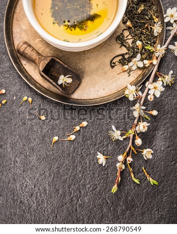 Cup of green cherry tea on dark stone background, top view, place for text - stock photo