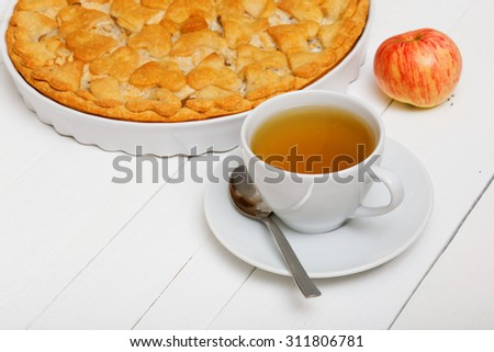 Cup of green tea and homemade pie with apples and pears on white wooden table