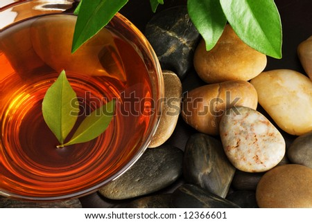 Cup of green tea and multicolored pebbles - stock photo