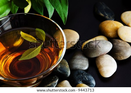 Cup of green tea and pebbles - stock photo