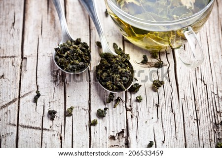 cup of green tea and spoons on rustic wooden table  - stock photo