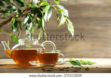 Cup of green tea on table on wooden background - stock photo