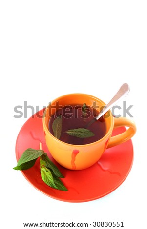 Cup of green tea on the saucer with mint