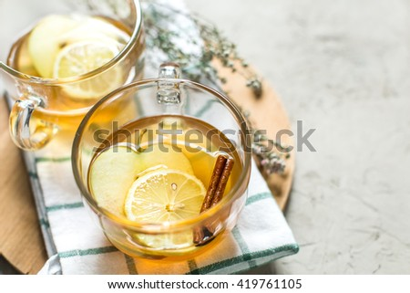 Cup of green tea with cinnamon, lemon and apples