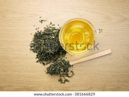 Cup of green tea with dried green tea leaves on wooden background.View from the top. - stock photo