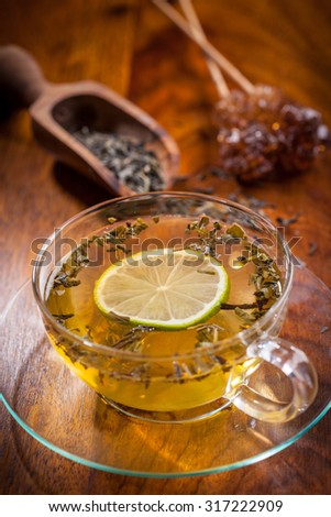 Cup of green tea with dried tea leaves - stock photo