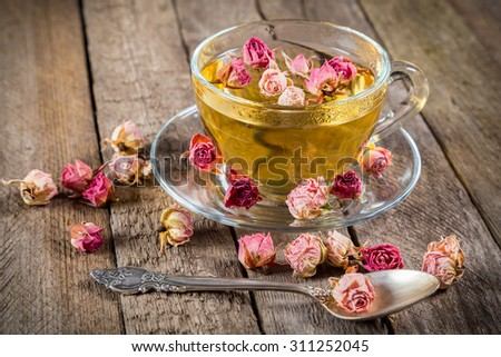 Cup of green tea with teaspoon and dried rose buds on old wooden table - stock photo