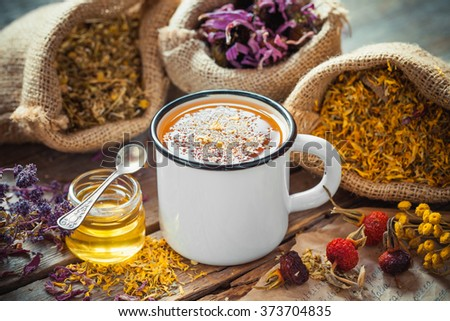 Cup of healthy daisy tea, honey and healing herbs. Herbal medicine.