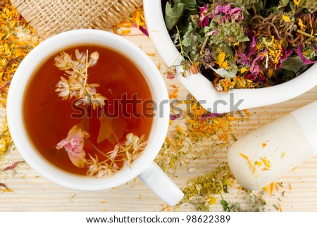 cup of healthy tea, mortar and pestle with healing herbs on wooden table, herbal medicine - stock photo