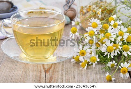 Cup of herbal chamomile tea on a wooden table. Chamomile tea in a transparent cup and camomile flowers on wooden table. Herbal tea for baby's stomach. Copy space. - stock photo