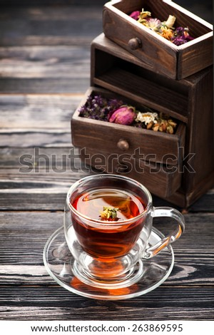 Cup of herbal tea and dried herbs - stock photo