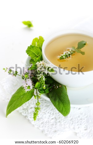 cup of herbal tea and edible flowers on a white background - stock photo