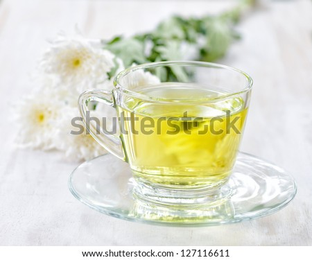 Cup of herbal tea and flowers. - stock photo