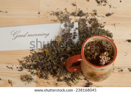 Cup of herbal tea.  Good morning note on the wooden table