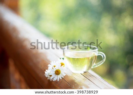 Cup of herbal tea on the railing of the balcony. - stock photo