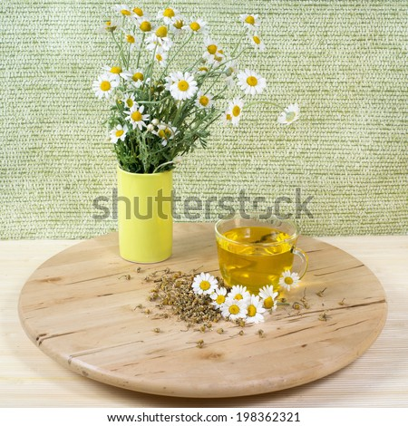 Cup of herbal tea with chamomile flowers on wooden table - stock photo