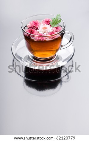 cup of herbal tea with flowers on black - stock photo