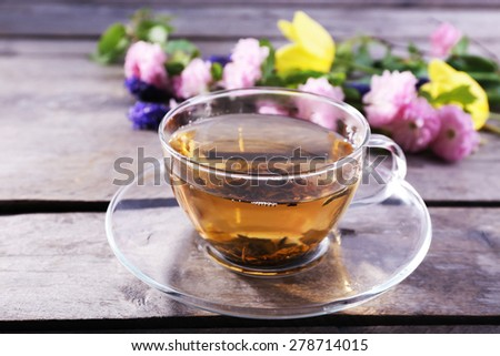 Cup of herbal tea with flowers on wooden table, closeup - stock photo