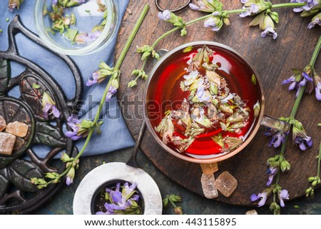 Cup of herbal tea with fresh herbs and aged vintage tea set, top view, close up. Healthy ,healing or detox drinks concept - stock photo