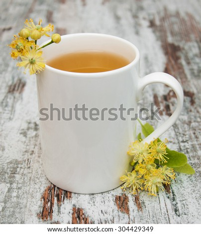 Cup of herbal tea with linden flowers on a old wooden background - stock photo