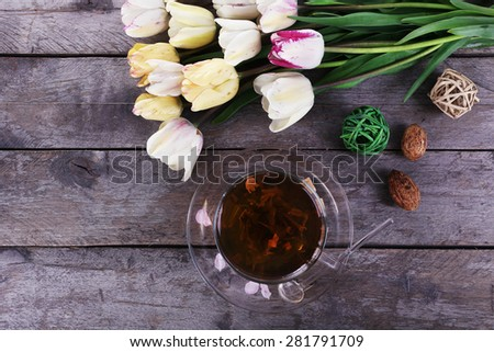 Cup of herbal tea with tulips on wooden table, top view - stock photo
