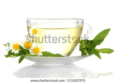 Cup of herbal tea with wild camomiles and mint, isolated on white