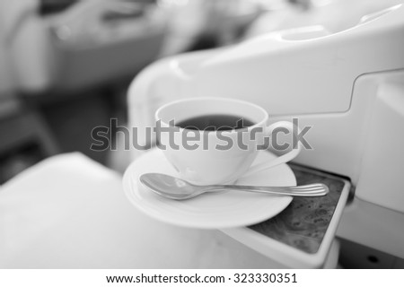 Cup of hot black tea served in business class - stock photo
