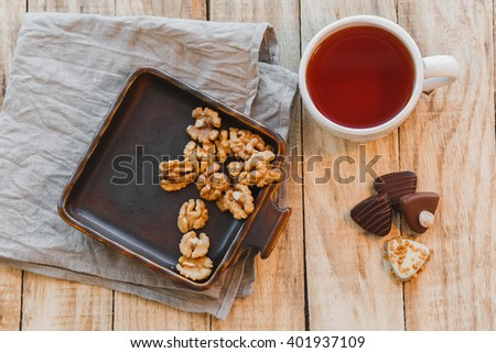 Cup of hot black tea with chocolate candy and walnuts on wooden table, flat lay, selective focus - stock photo