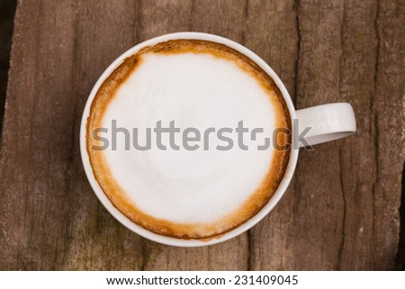 Cup of hot cappuccino coffee on wooden table. - stock photo