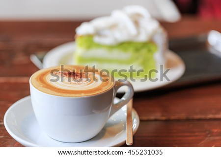 cup of hot cappuccino coffee with cake on wood table - stock photo