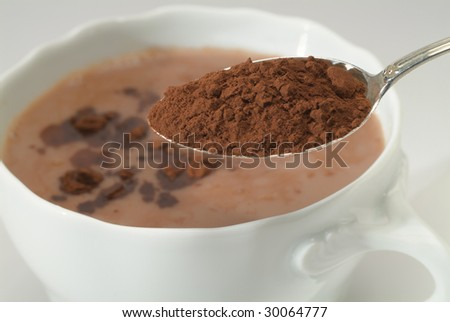Cup of hot chocolate and teaspoon with cacao - stock photo