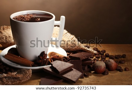 cup of hot chocolate, cinnamon sticks, nuts and chocolate on wooden table on brown background - stock photo