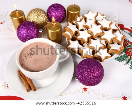 Cup of hot chocolate with cinnamon, star shaped christmas cookies with icing and gold candles with christmas balls on christmas tablecloth - stock photo