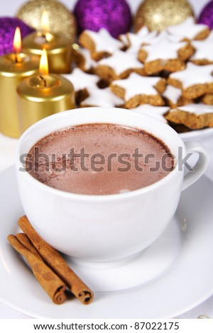Cup of hot chocolate with cinnamon sticks, star shaped christmas cookies with icing, gold candles and christmas balls - stock photo