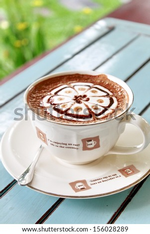 Cup of hot chocolate with flower pattern cream on wood table - stock photo