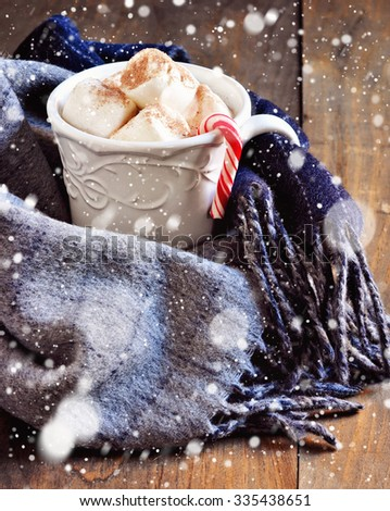 Cup of hot chocolate with marshmallows and candy, winter scarf, Christmas decoration, holiday, selective focus, toned image, falling snow effect - stock photo