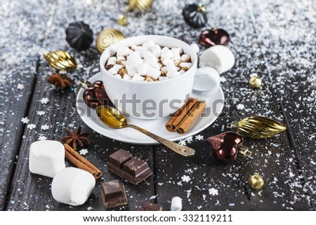 Cup of hot chocolate with marshmallows and christmas ornaments on snowy table - stock photo