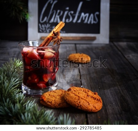 cup of hot Christmas mulled wine with cake - stock photo