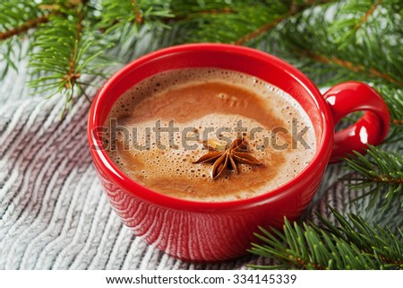 Cup of hot cocoa or hot chocolate on knitted background with fir tree, traditional beverage for winter time - stock photo